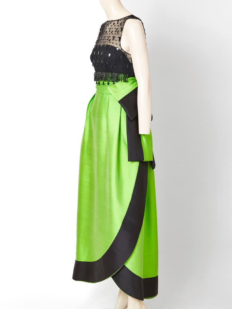 Attributed to Irene Galitzine, sleeveless gown, having a black net bodice embellished with jet beads and sequins. Skirt of the dress is a structured shape, in an emerald  green, tone, having a cummerbund and a two tone large bow.The hem is curved