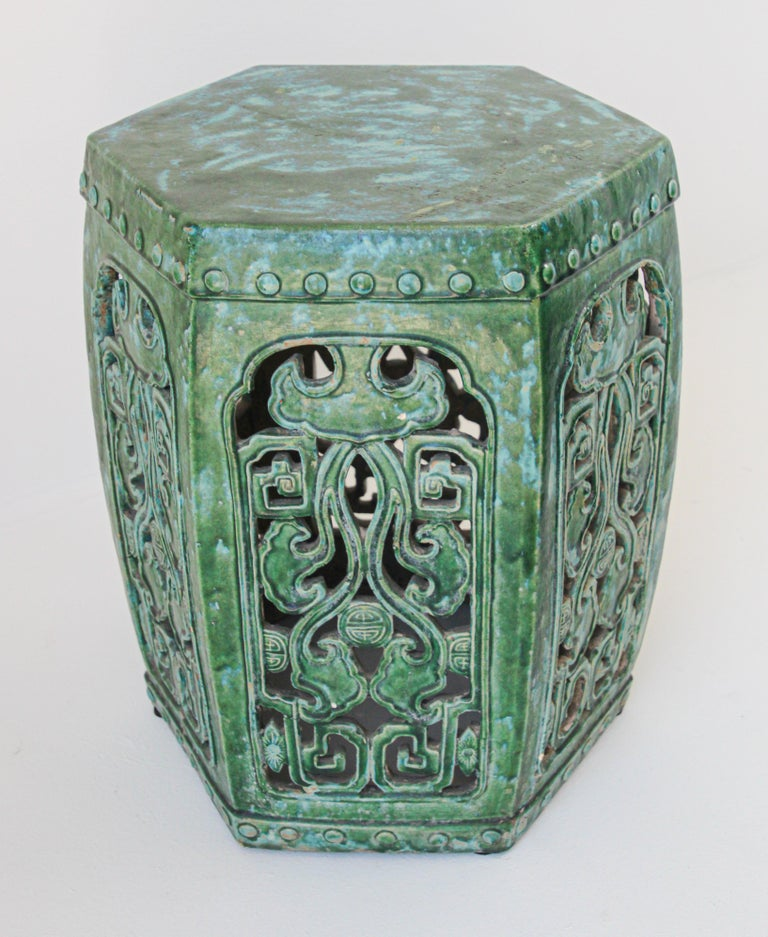 Large emerald green Chinese ceramic garden stool. Nicely carved on each sides with Fen Shui designs and foliages with raised dots around top. Chinese export emerald green ceramic glaze stool great to use indoor or outdoor as a stool, end table, or