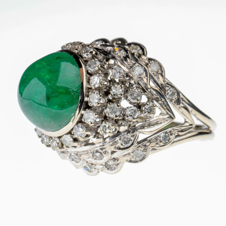 An over 5 ½ carat bright, soulful emerald cabochon measuring  11.23 mm x 10.79 mm is perched atop a hand-fabricated 14k white gold scaffolding in a kind of chevron configuration that supports 54 single-cut diamonds. This ring is bold, audacious,