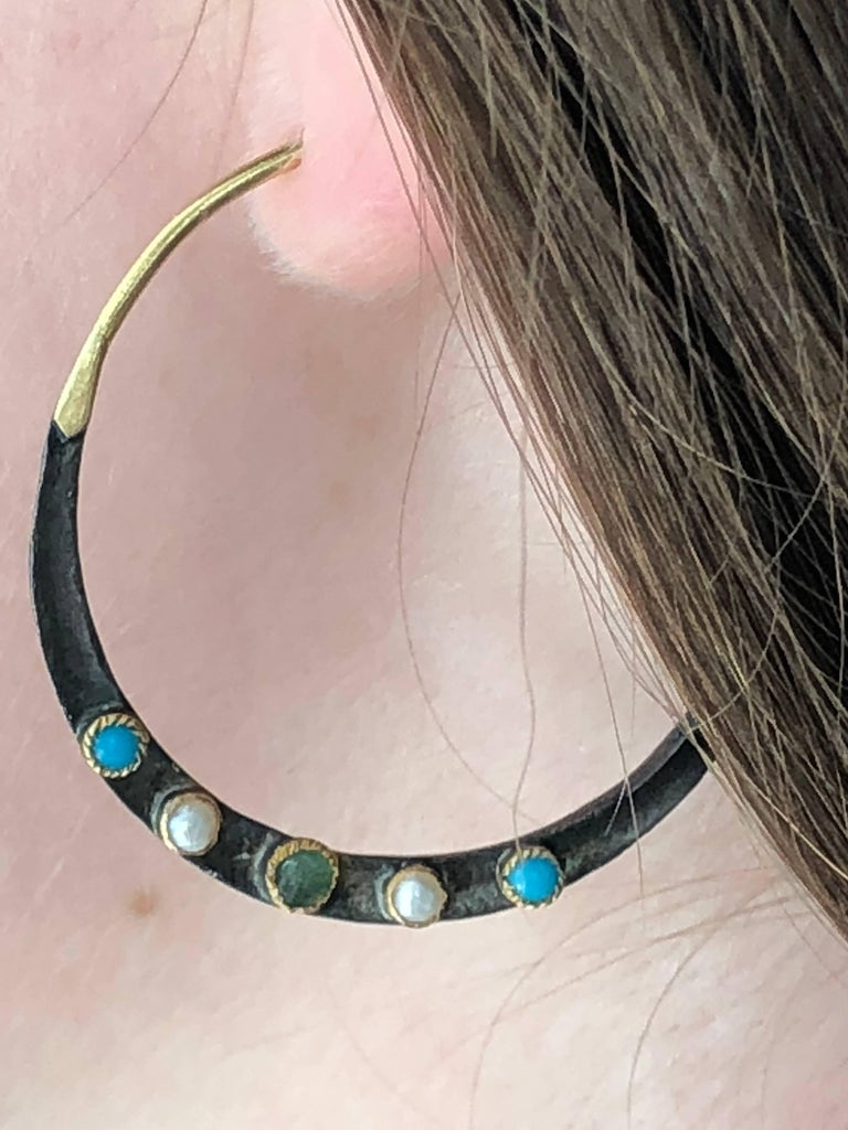 The hoop earrings HOLY are hand made and designed in Paris. Made in 14K gold and oxidized sterling silver, the earrings are enhanced by emerald ( 0,45 ct.), turquoises and pearls.  Brand : 5 OCTOBRE Designer : Sophie Pfeffer