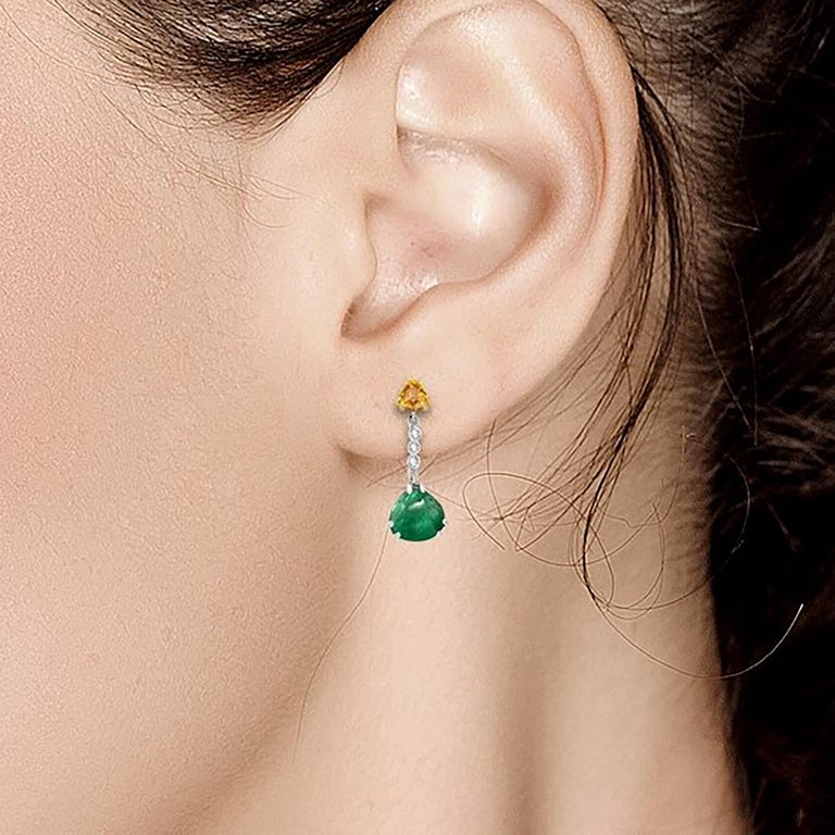 Fourteen karat white and yellow  gold drop earrings  Two triangle shaped cabochon emerald weighing 4.81 carat  Yellow sapphire weighing 0.85 carat  Diamonds weighing 0.15 carat Earrings measuring 1