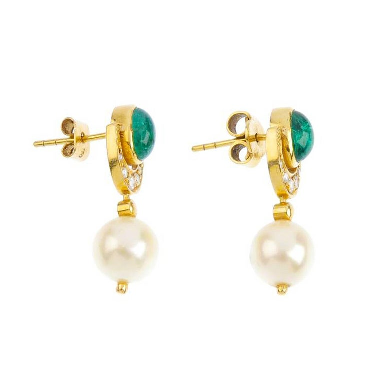 18ct gold, emerald, cultured pearl and diamond earrings. Each designed as a cultured pearl, measuring 10mms, with brilliant-cut diamond crescent and oval emerald cabochon surmount. Estimated total diamond weight 0.20ct. Length 2.8cms. Weight 7.2gms.