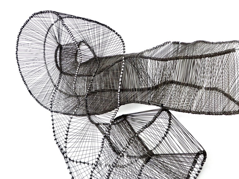 Chicago based artist Eric Gushee, has created a body of work called the Emergence Series. This sculpture is a piece unique variation, incorporating the Mobius strip as a design structure. Made of stainless steel and black anodized steel wire, the
