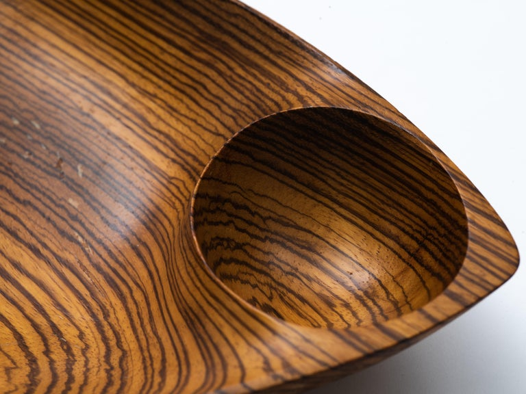 """A hand carved, double-compartment freeform bowl with handle by Emil Milan (1922-85). Milan referred to his handcrafted accessories as """"functional sculpture"""" and this rare example executed in zebra wood certainly exemplifies why. Rich patina"""