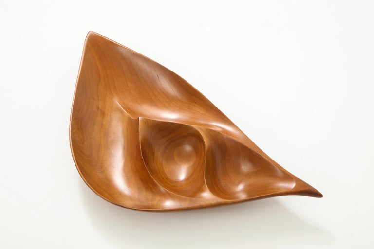 Finely carved, freeform segmented dish in cherry wood, created circa 1960s, by esteemed midcentury woodworker Emil Milan (1922-85). Trained at the Arts Students League of New York, Milan worked in the metropolitan New York area until relocating to