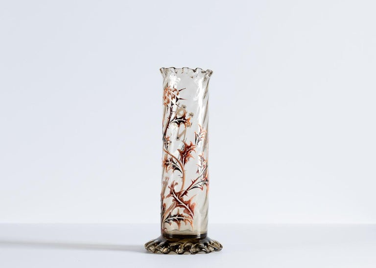 This trio of cylindrical, diagonally ribbed vases comes from one of the Art Nouveau's great masters, the French artist Émile Gallé. The pieces, executed in one his preferred mediums, enameled glass, depict thistles in muted reds and browns, and rest