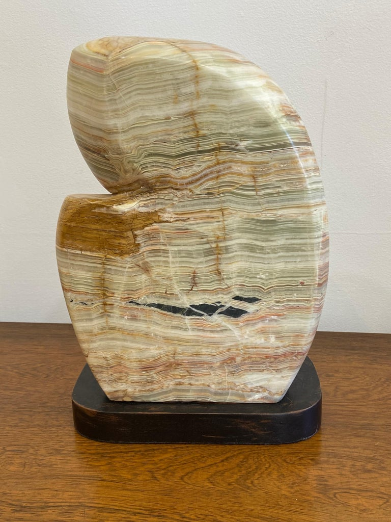 Abstract agate sculpture on wood base.