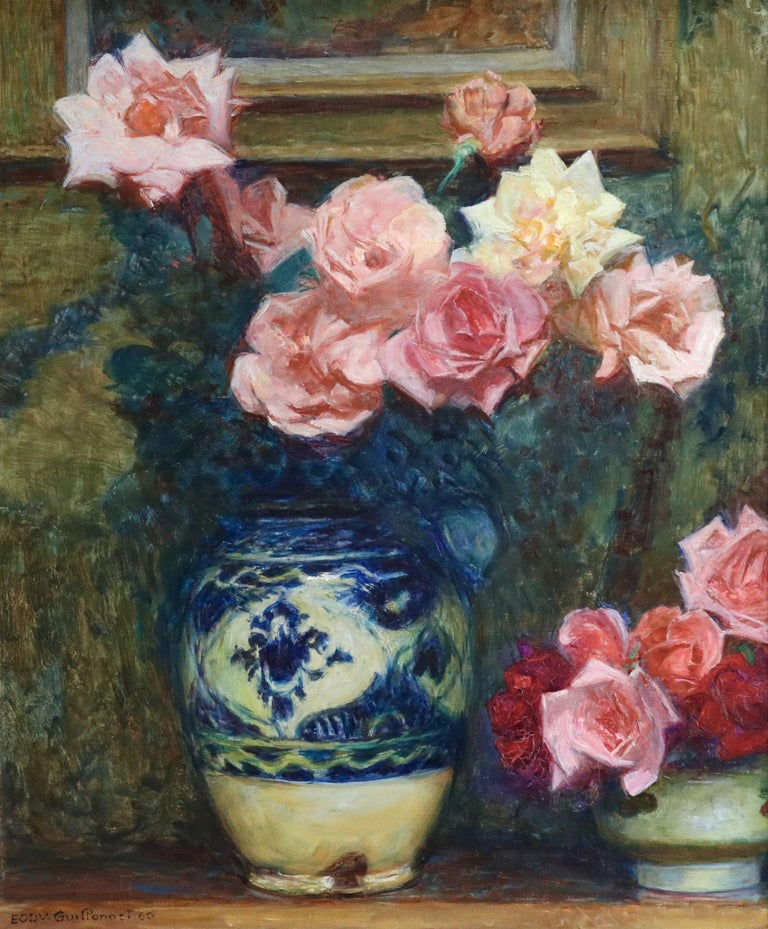 Oil on original canvas by Emile Octave Denis Victor Guillonnet depicting pink roses in a blue and white vase on a table with a frame hanging behind it. Signed lower left and dated 1960. Framed dimensions are 28 inches high by 24 inches wide.  Émile
