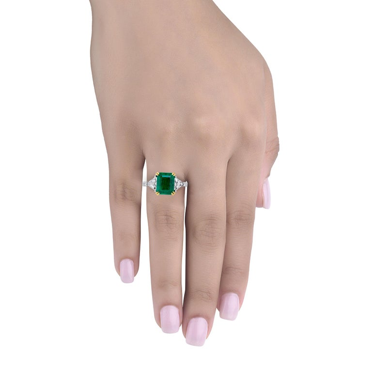 Hand made in Platinum in the Emilio Jewelry factory!  Center Stone: 3.32ct genuine certified zambian emerald of rich green color and totally eye clean 9.80mmx8.00mm  Diamonds: Flanked by 2 Trilliant cut emeralds and round diamonds down the shank