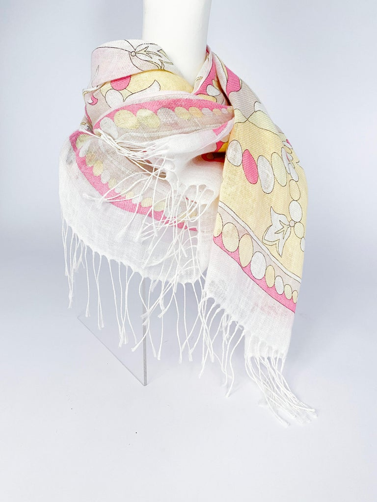Emilio Pucci linen scarf featuring an abstract printed motif with tones of green, pink, beige, green, and yellow. The ends are finished with fringe.