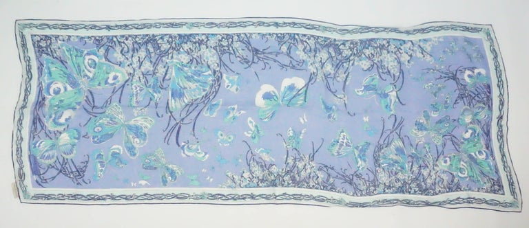 Emilio Pucci Blue Print Cotton Shawl  This Pucci cotton large scarf/shawl is made up of different shades of blues. There are butterfly shapes throughout the scarf and a boarder that contains a design of woven lines. This item is in good vintage