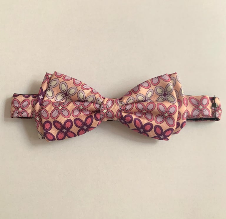 Emilio Pucci pre-tied adjustable pink and purple Pucci print bow tie. Pink and purple pattern resembles petals that have been fastened together with stitches. Fastens with hook that attaches beneath shirt collar.  100% silk.  Made in Italy.