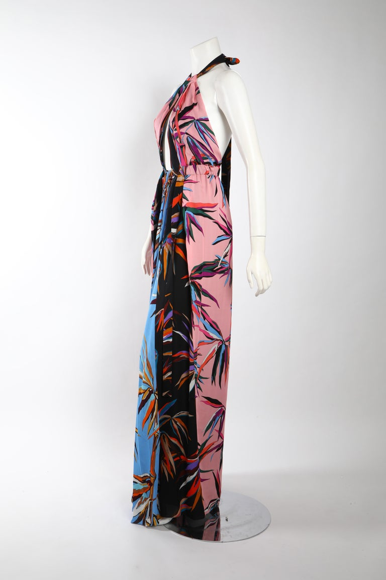 Printed floor length gown in tones of pastel pink, sky blue, and navy by Emilio Pucci. Draped silhouette with keyhole opening above the bust line and halter neck tie. Size US 2/ IT 38.