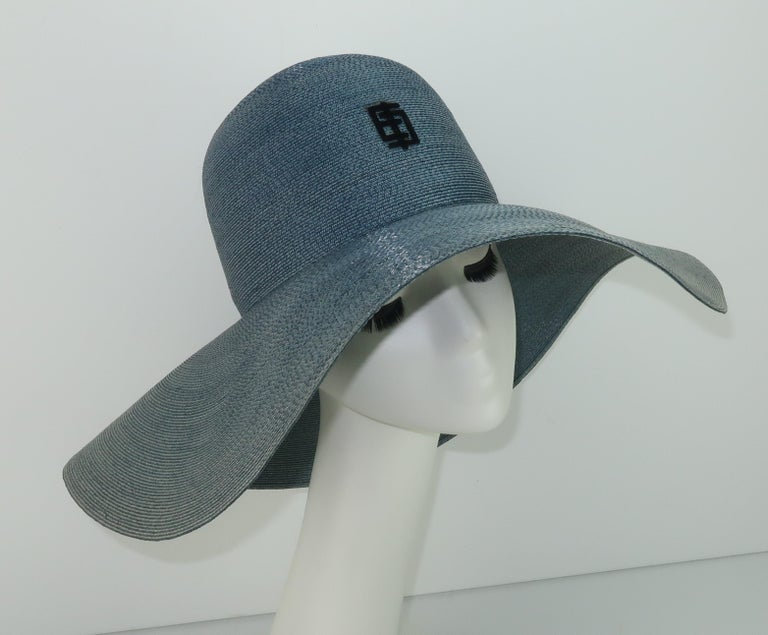 1960's Emilio Pucci floppy wide brim straw hat in a blue-gray shade reminiscent of denim with black velvet stylized 'EP' logo at the crown.  The chic floppy style is perfect for sun shade or traveling incognito.  Originally retailed at Saks Fifth