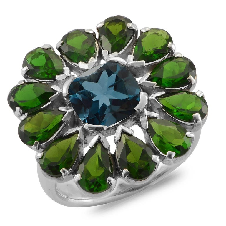 This stunning statement ring has been handmade in our workshops. It is one of a kind ring made in sterling silver and has a central dazzling blue topaz, surrounded by petals of chrome diopside. If you love blue and green then this is the ring for