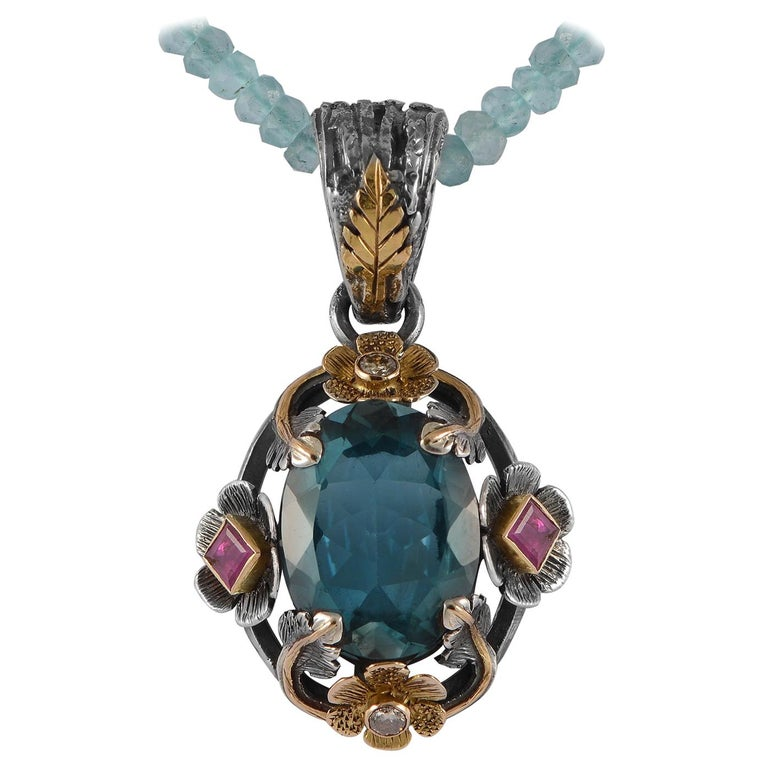 This exquisite one of a kind pendant, earrings and ring suite has been handmade in our workshops. The jewellery features blue topaz, set on oxidised silver, overlaid with 18ct gold floral motifs. The gold motifs are embedded with rubies and