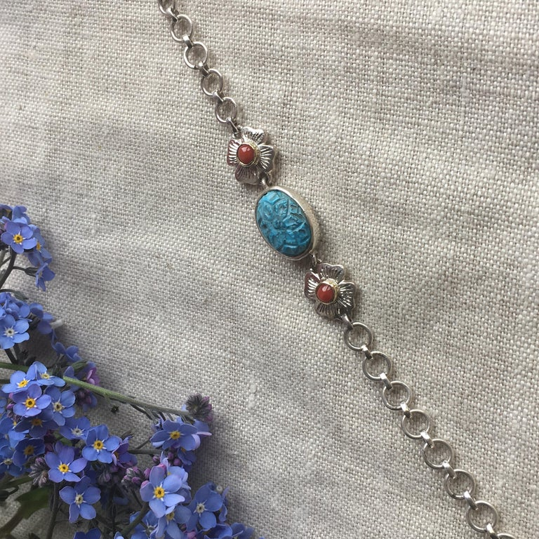This lovely bracelet has been handmade in our workshops. Using hand carved turquoise we have mixed it with coral which is set in hand engraved floral motifs all made in sterling silver. The bracelet is adjustable so will fit anyone. Wear it to enjoy