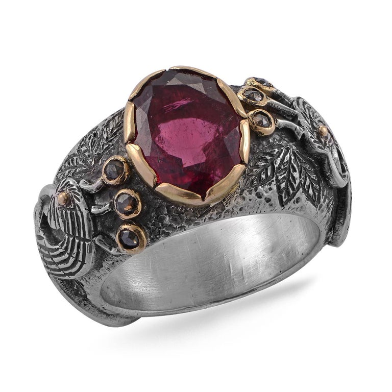 This stunning one of a kind ring, has been handmade in our workshops. It features a large central rubelite tourmaline set in 18ct gold. The sides of the ring which are made of oxidised sterling silver,  has hand engraved peacocks on them and the top