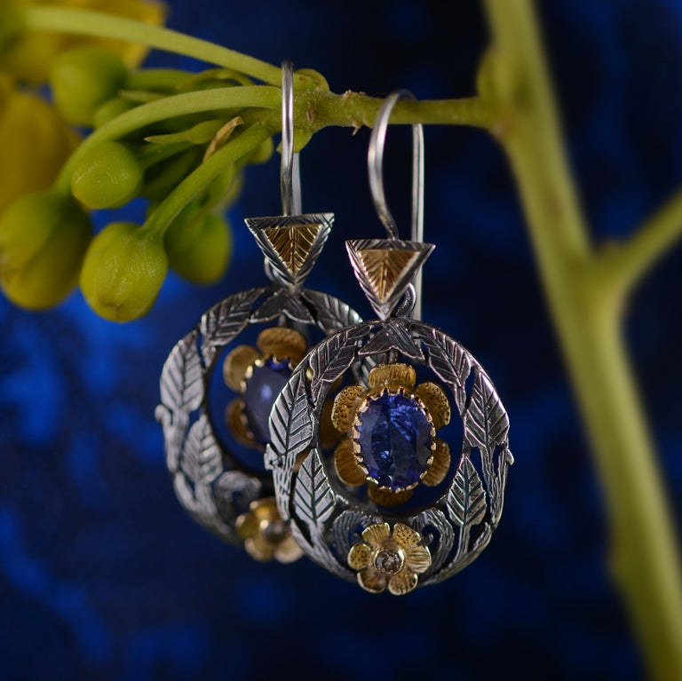 These exquisite one of a kind earrings have been handmade in our workshops. Using oxidised silver and 18kt gold, they are embedded with diamonds and have moving tanzanite drops. They have intricate hand engraving work on them in the shapes of mughal