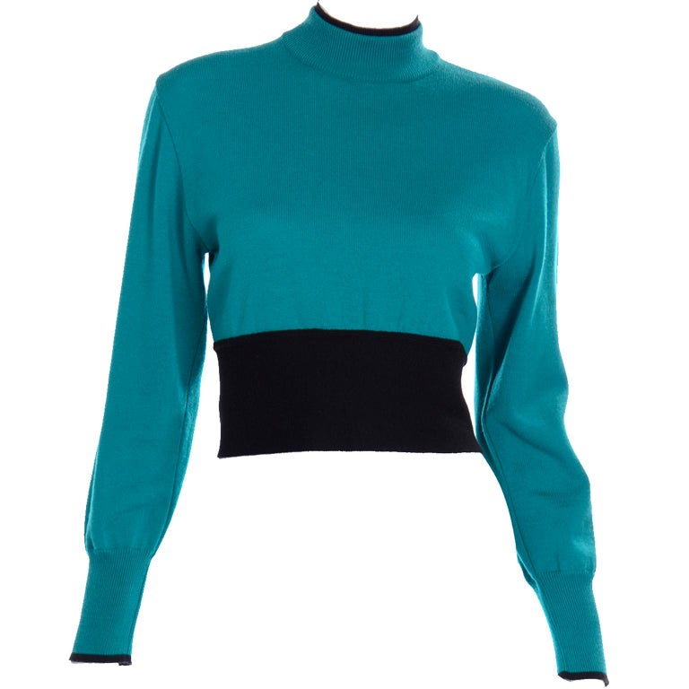 This vintage Emmanuelle Khanh teal wool sweater has a beautiful navy blue sash. The collar of the sweater top is a mock neck and has two layers, one being navy blue and the other teal. The sleeves are long and have a small navy blue tip at the