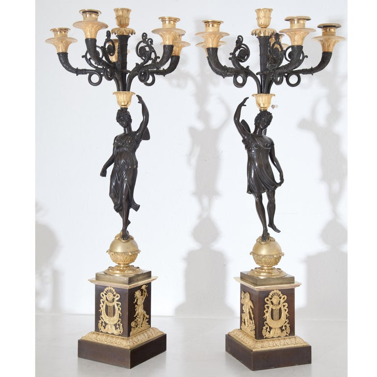 Pair of six-flamed girandoles with winged psyches on spheres, balancing the chandelier on their heads. Burnished square pedestals with lyre and Amoretti decoration. Bronze, fire-gilt. (measurements plinth: 13 x 13 cm).