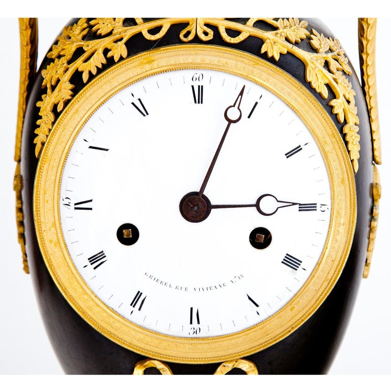 Empire clock in an Amphora-shaped case with swan-neck handles, partly burnished and gilt. The enamel clockface with Roman hours and Arabic minutes is signed Griebel Rue Vivienne No. 13. For a similar piece, see Lit.: Pierre Kjellberg: Encyclopédie