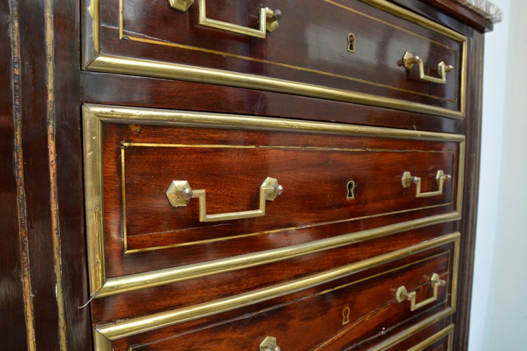 Empire dresser or secretary, Paris, 1810s. Made of mahogany.  Feet with fine brass applications. Eight drawers with fine, circumferential brass strips, two handles each, key inlays also in brass, original marble top. Lateral pilaster strips each