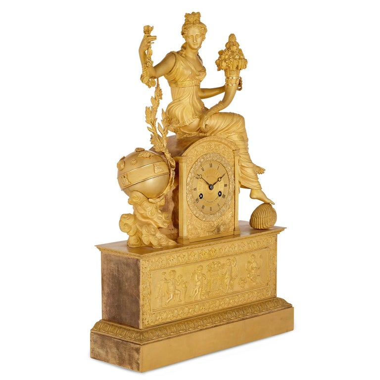 This large and impressive gilt bronze mantel clock is by the French Michel-François Piolaine. The clock body is raised by an architecturally formed, plinth-shaped base, set to the front with a relief scene, also of gilt bronze, portraying four putti