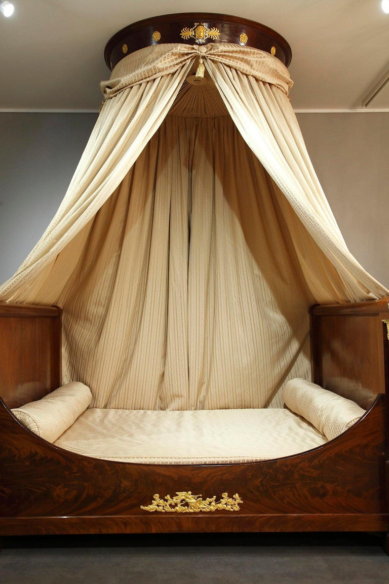 Early 19th century Empire-period monumental slight bed crafted from molded mahogany, mahogany veneer and gilt bronze. Sleigh bed is defined as a style of bed with curved or scrolled headboards and footboards thus resembling a sled or sleigh. The
