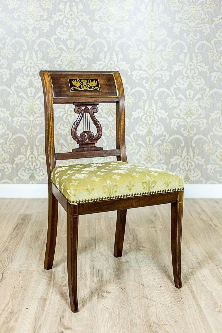 We present you this set of three chairs in the Empire style, made of solid mahogany wood. The chairs are of a classicizing form, with saber-like legs, and a softly upholstered seat. Furthermore, the back splat has a wide, rolled outwards top rail,