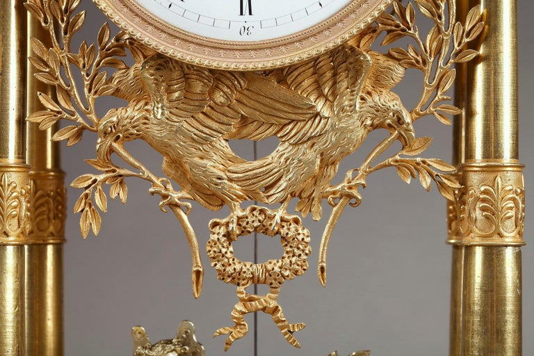 Empire mantel clock in ormolu, or gilt bronze, designed as a portico, with four columns decorated with foliage and palmette. The columns support the entablature embellished with Pegasus and topped by a putto sculpting an antique bust. The dial with