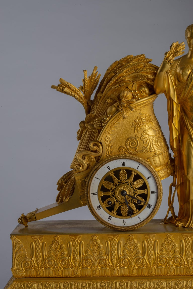 The rectangular base decorated with a wheat and foliate frieze and raised on four ball feet, the goddess of agriculture Ceres standing while leaning against a Roman chariot with harvested wheat, the dial with roman numerals forming its wheel.