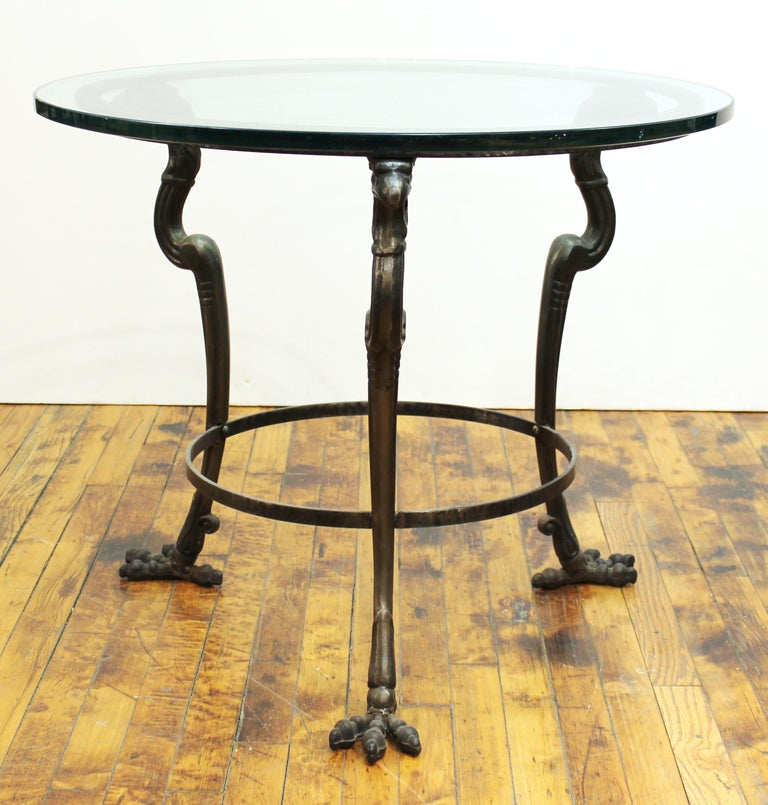 Empire revival style modern tripod center table or side table with eagle heads and claw feet and circular glass top.