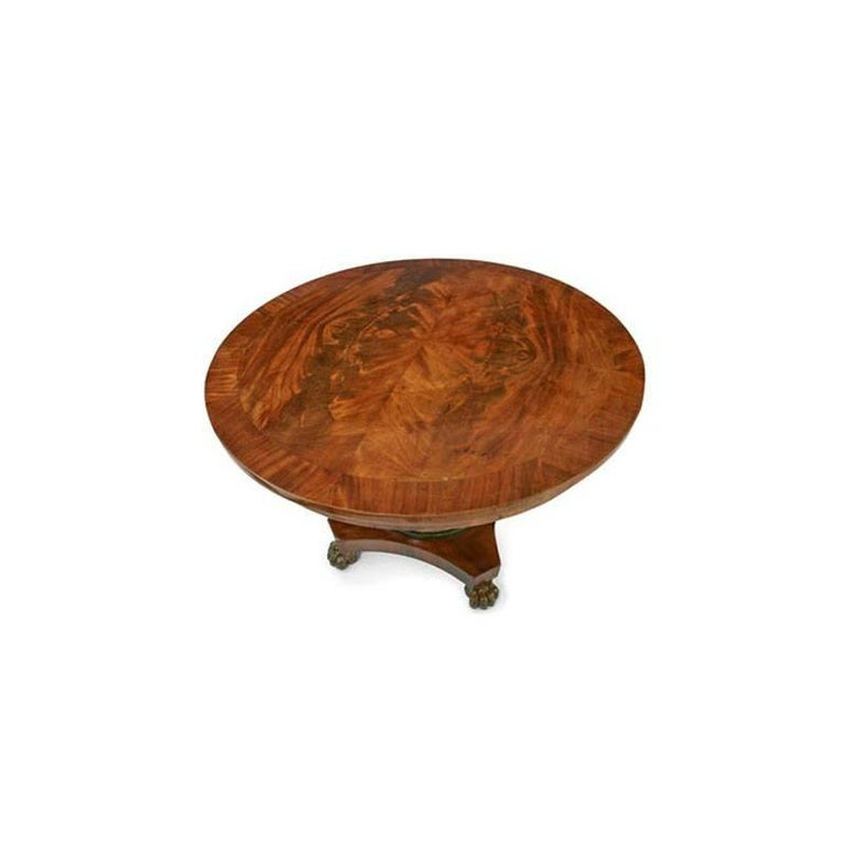 Mahogany veneered round tabletop with a mirrored pattern, a veneered skirt and vase shaped Stand in dark green with gilt details, on a stepped quatrefoil base with lion's feet.
