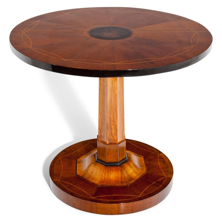 Empire salon table on a round base with an octagonal column and a round tabletop. The base and top are decorated with Fine thread inlays. The tabletop shows an Amphora with flowers, painted in ink. The tabletop folds down. The table is in a