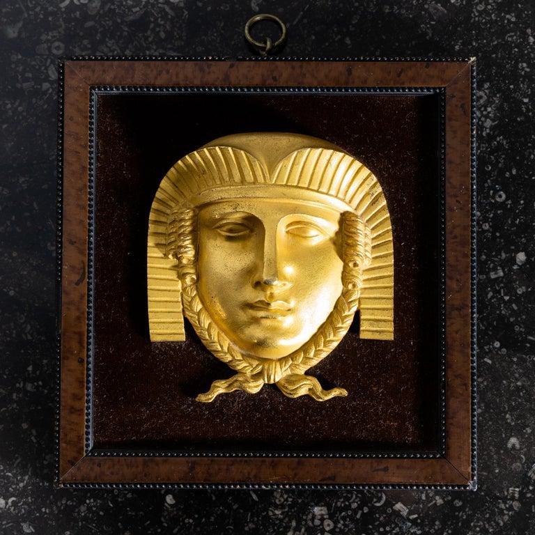Maskaron der Sphinx aus feuervergoldeter Bronze im quadratischen Rahmen auf Samt gerahmt.