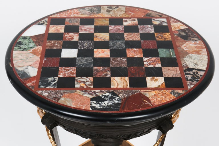 Empire style Grand Tour bronze gueridon or pedestal table with a circular pietra dura marble games top, gilt bronze rams head, paw feet, and swag details, mounted on square platform base. In great antique condition with age-appropriate wear and