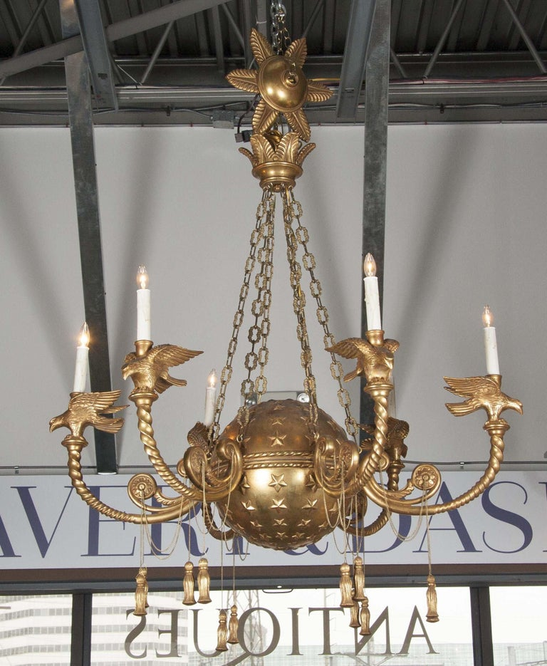 A French Empire style carved gilt chandelier with star relief globe, and eagle arms.