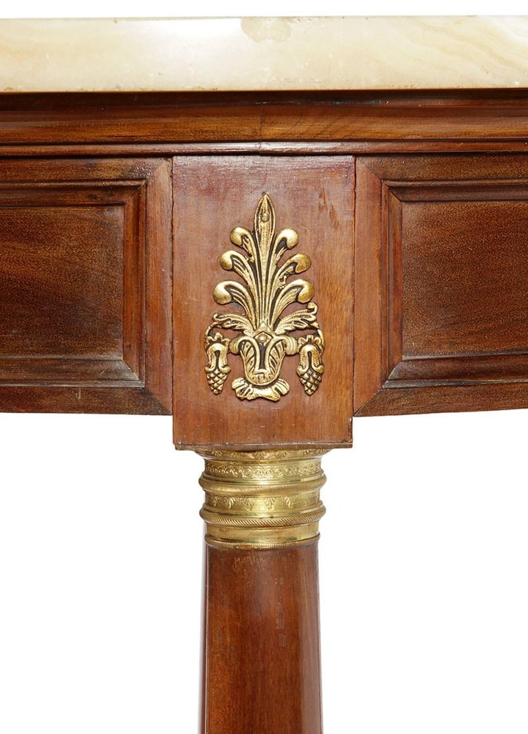 Auxiliary table Empire style, with structure in wood in its color, ornamental applications in bronze and onyx bronze. Of circular plan, it rises on four legs in the form of a column, united by a molded