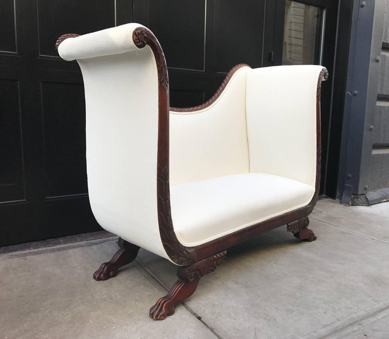 Empire style tall back loveseat with carved mahogany base and claw feet. Newly upholstered in off-white fabric.
