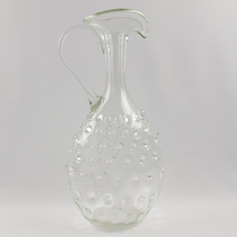 Elegant 1950s, tall pitcher or decanter manufactured by Empoli, Italy. Beautiful highly decorative Etruscan shape with hobnail pattern. Hand blown glass in Murano, Italy. Measurements: 7.87 in. wide (20 cm) x 5.12 in. deep (13 cm) x 15.37 in. high