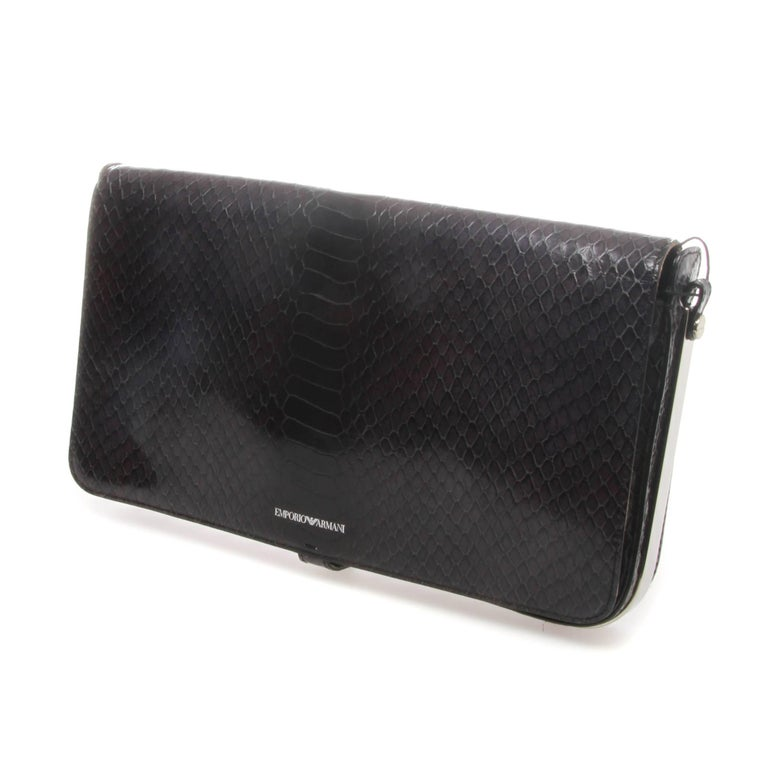 Emporio Armani clutch in navy blue faux snakeskin featuring a hinged opening/closing mechanism with silver-tone metal trimming and push stud fastening at bottom. Detachable 120cm shoulder strap. Silk lining.