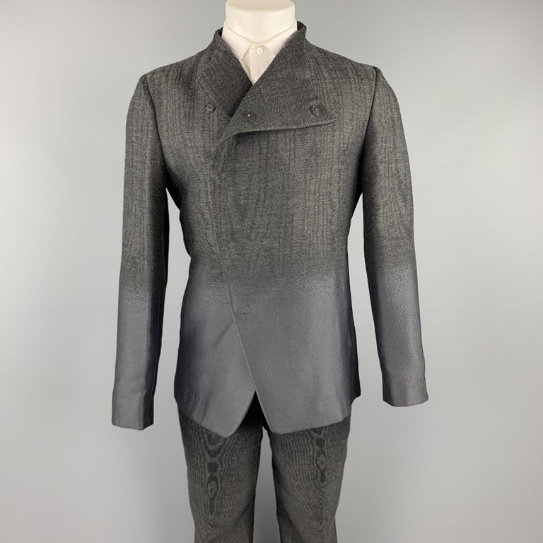 EMPORIO ARMANI suit comes in charcoal ombre with a half liner and includes an asymmetrical snap button sport coat with a collarless lapel and matching flat front trousers. Made in Italy.  Excellent Pre-Owned Condition. Marked: IT