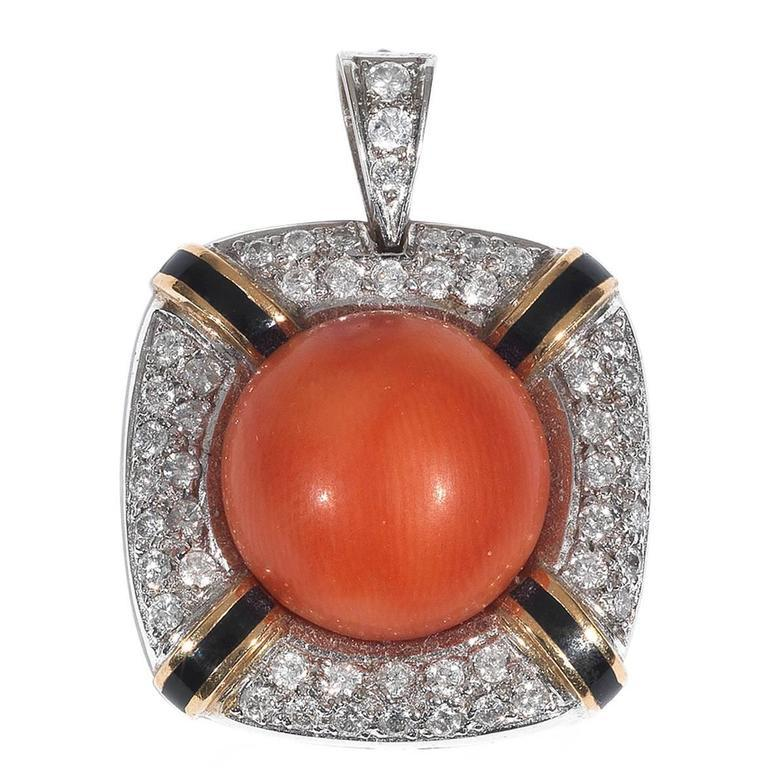 Of rounded corners square shape design centered by a round cabochon coral measuring approx. 15 mm framing by a diamond pave set and black enamel rows border.  Mounted in 18Kt white and yellow gold.  34 mm long   Weight: 17.9 gr
