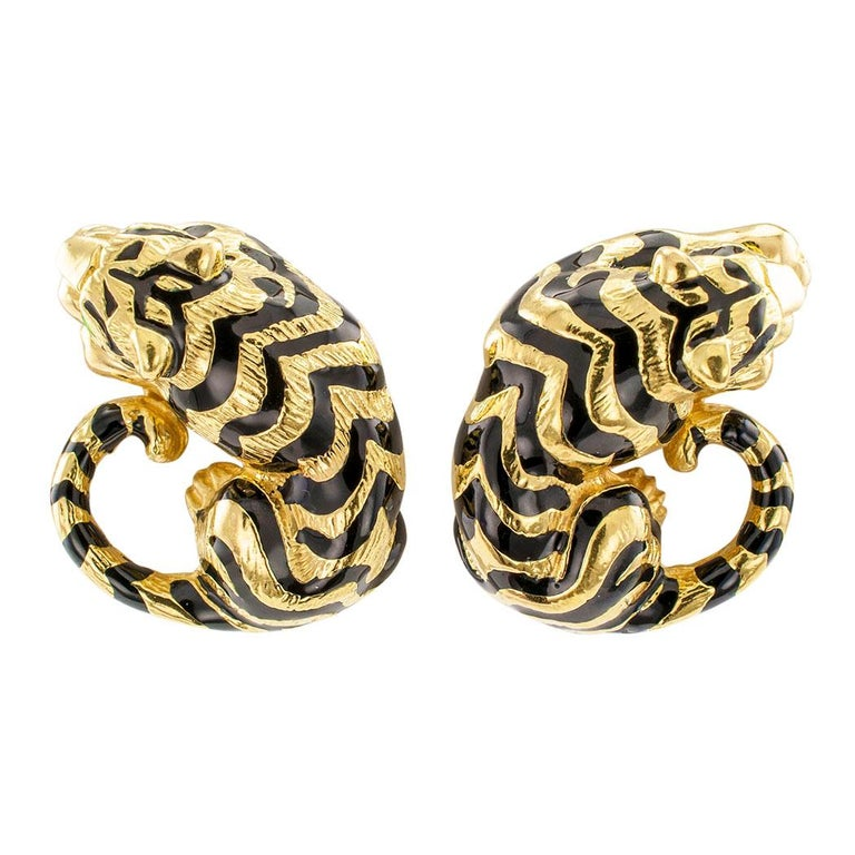 Enamel and gold tiger ear clips circa 1980. Matching figural designs depicting a pair of resting tigers, their bodies accented with black enamel tiger stripes, the eyes green enamel, crafted in 18-karat yellow gold. These gorgeous tiger earrings are