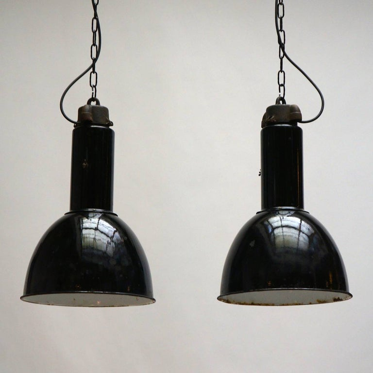 Two very similar Industrial factory pendant lights, in black enameled steel. Wired and ready to be hung. Measures: Diameter 36 cm. Height 55 cm. Total height with the chain is 100 cm.