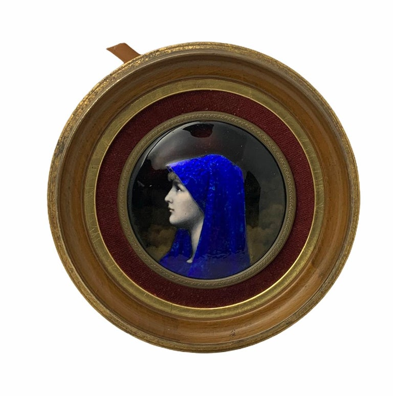 This is an enamel portrait of Fabiola framed in a small round wood plaque. Fabiola was a member of a wealthy Roman patrician family. She devoted herself to charitable works. She built the first Christian public hospital in the west. The portrait