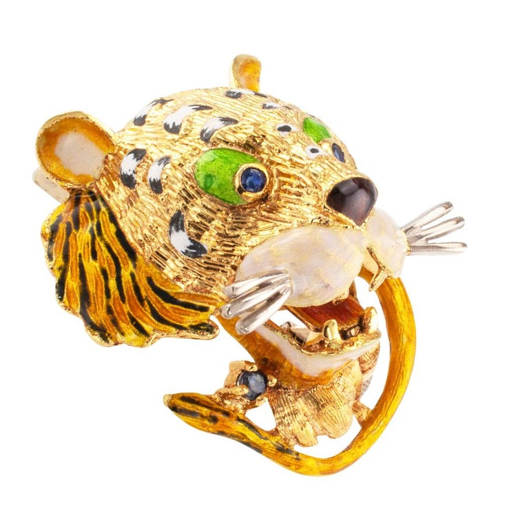 Enamel tiger brooch with sapphires mounted in 18 karat gold circa 1960. The design features the head, tail, and front paws of a tiger seemingly lunging forward, decorated with enamel,  and sapphire eyes, mounted in 18-karat gold. It is beautiful and