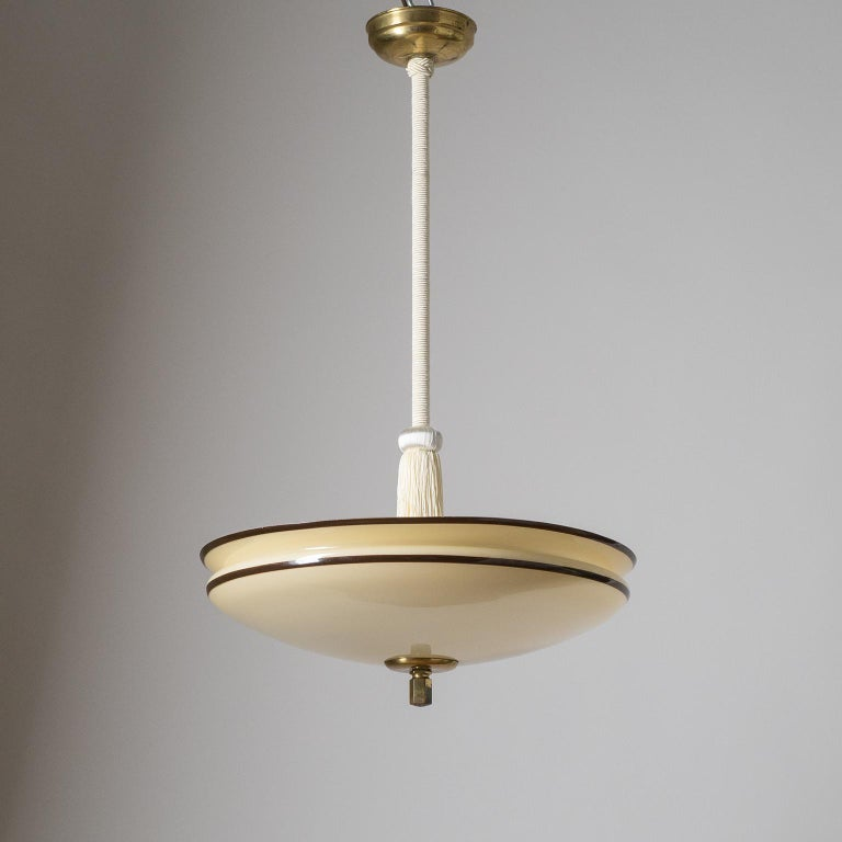 Art Deco pendant from the 1930s with an enameled glass diffuser. The shallow bowl shaped glass is sand-colored with a white inner casing and has two dark brown stripes painted along the rim. Stem with off-white passementerie trimmings and tassel.