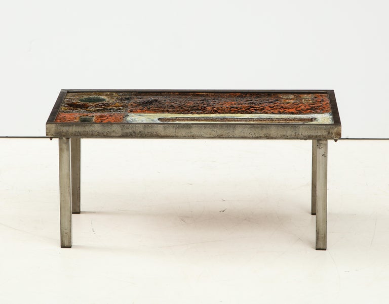 Rare low coffee table by Robert and Jean Cloutier, France, circa 1950.   This coffee table consists of brushed steel legs and a stunning enameled lava top with an explosive design that invokes the painterly feats of Abstract Expressionism. Its warm,